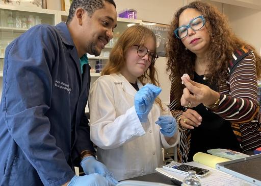 La Dra. Carmen Maldonado Vlaar con dos miembros de su laboratorio, examinando un tubo de muestra.
